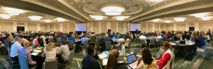 Midwest Leadership Summit attendees seated at round tables working on leadership strategies.
