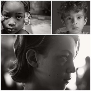 Three faces of children with sad expressions in black and white.